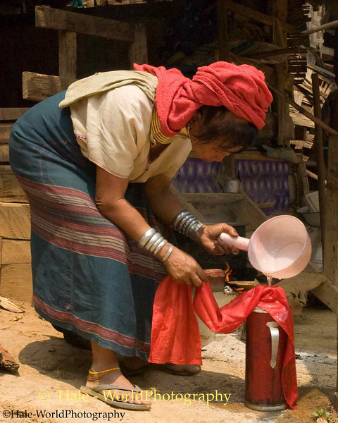 Padaung Woman Straining Tea or Coffee in Huay Sua Tao Refugee Camp
