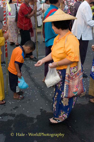 Young Shan Boy Receiving Popped Rice Offering From Shan Woman During Poi Sang Long Festival, Maehongson, Thailand