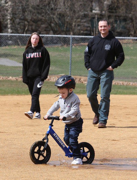 People enjoy spring weather at Shedd Park during Covid-19 emergency. Duke Petterson, 3, of Westford, rides his bike through a puddle in the infield at Shedd Park, followed by his sister Maya Petterson, 14, of Lowell, and father Mike Petterson of Westford. (SUN/Julia Malakie)