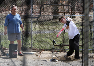 People enjoy spring weather at Shedd Park during Covid-19 emergency. Alex Wyman, 14, of Lowell, an 8th grader, hits baseballs in the batting cage at Shedd Park, with his father Wayne Wyman supplying the balls. He plays in the Shedd Park Senior League but they don't know when the season will start, due to the Covid-19 emergency. (SUN/Julia Malakie)