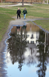 People enjoy spring weather at Shedd Park during Covid-19 emergency. Walkers who did not want to give names, do laps at Shedd Park, reflected in a large puddle. (SUN/Julia Malakie)