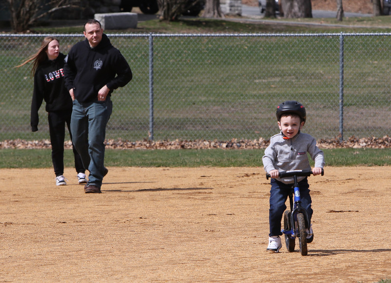 People enjoy spring weather at Shedd Park during Covid-19 emergency. Duke Petterson, 3, of Westford, rides his bike around the infield at Shedd Park, followed by his sister Maya Petterson, 14, of Lowell, and father Mike Petterson of Westford. (SUN/Julia Malakie)