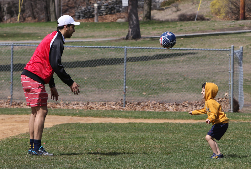 People enjoy spring weather at Shedd Park during Covid-19 emergency. Elton Melo of Lowell and his son Artur Philip, 4, play with a soccer ball. (SUN/Julia Malakie)