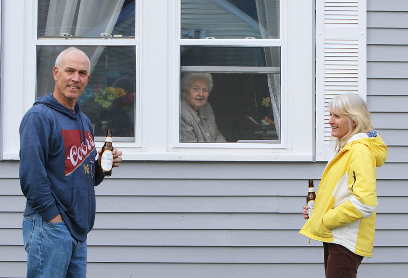 "Dave and wife Gina MacLure of Westford visit Gina's mother, Marian ""Mimi"" Bumann of Shirley, on her 87th birthday, social distancing through the window during the Covid-19 emergency. The MacLures were enjoying Yuengling pilsner, which Dave said is from the oldest brewery in the U.S., in Pennsylvania. (SUN/Julia Malakie)"