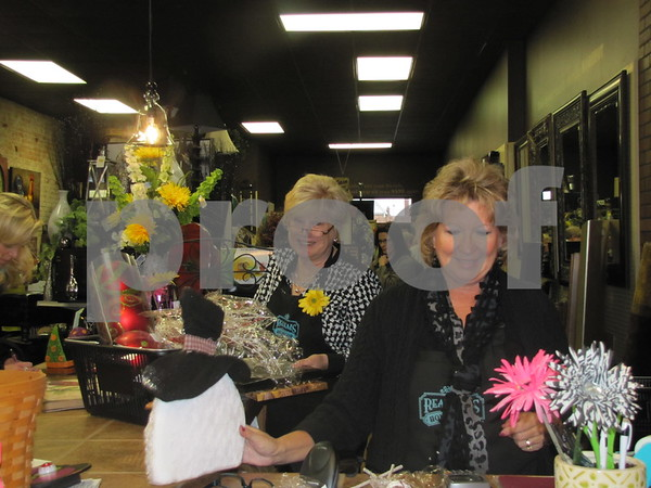 Beth Plautz and Jean Doyle wrap up customer purchases at their store 'Real Deals'.