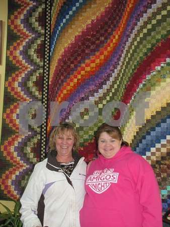 Mary Vollmer and Sally Kiecker standing in front of one of the beautiful quilts on display at 'Tillie's Quilts' in downtown Fort Dodge.