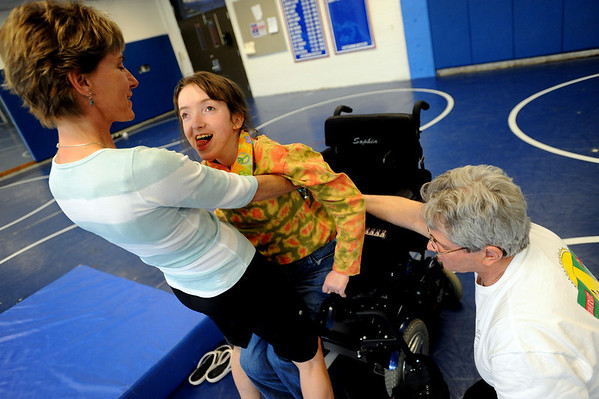 "Physical therapist, Janice Moore, left, helps Sophia Ruggeri, as  her father Jay,  encourages her to stand up.<br /> Sophia Ruggeri, a senior at Centaurus High School with special needs, and her father Jay, believe she should go to the same events as all the other students.They believe the school district shouldn't have special events for kids with special needs.<br /> For more photos and a video of the tour, go to  <a href=""http://www.dailycamera.com"">http://www.dailycamera.com</a>.<br /> Cliff Grassmick / April 28, 2010"