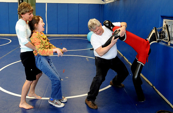 "Physical therapist, Janice Moore, left, helps Sophia Ruggeri, as  her father Jay,  horses around with a wrestling dummy to make her laugh.<br /> Sophia Ruggeri, a senior at Centaurus High School with special needs, and her father Jay, believe she should go to the same events as all the other students.They believe the school district shouldn't have special events for kids with special needs.<br /> For more photos and a video of the tour, go to  <a href=""http://www.dailycamera.com"">http://www.dailycamera.com</a>.<br /> Cliff Grassmick / April 28, 2010"