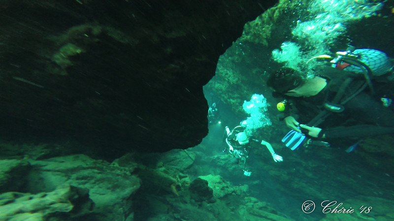 Danny, in the cenote, looks down on Edwin, who just excited the cave