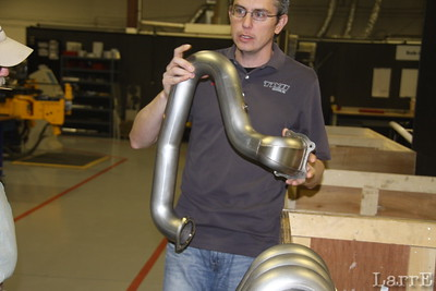 Mark holds one of the exhaust pipes that they bend in house.