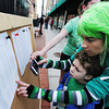 Globe/T. Rob Brown<br /> Stacey Gough and her six-year-old son, Braxton, both of Ozark, take a look at the results of the St. Patty's Revenge 5K Saturday morning, March 16, 2013, in downtown Joplin. Gough, who was one of many who dressed for the holiday, came in 40th place overall (15th place for women, and fourth place for women ages 30-34) with a time of 25:44.3.