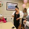 Marjorie Steele, an almost-lifelong resident of Arlington, now of Tewksbury, celebrates her 100th birthday today at Blaire House in Tewksbury. Granddaughters Shelby Steele of Tewksbury, center, and her sister Joie Steele of Providence, right, admire the Birthday Girl crown that Shelby said was payback for all the funny hats she had to wear as a child. (SUN/Julia Malakie)
