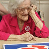 Marjorie Steele, an almost-lifelong resident of Arlington, now of Tewksbury, admires her Red Sox birthday cake as she celebrates her 100th birthday today at Blaire House in Tewksbury. (SUN/Julia Malakie)