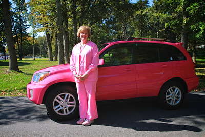 Dolly Wilson in front of her newly painted pink car, for breast cancer awareness.