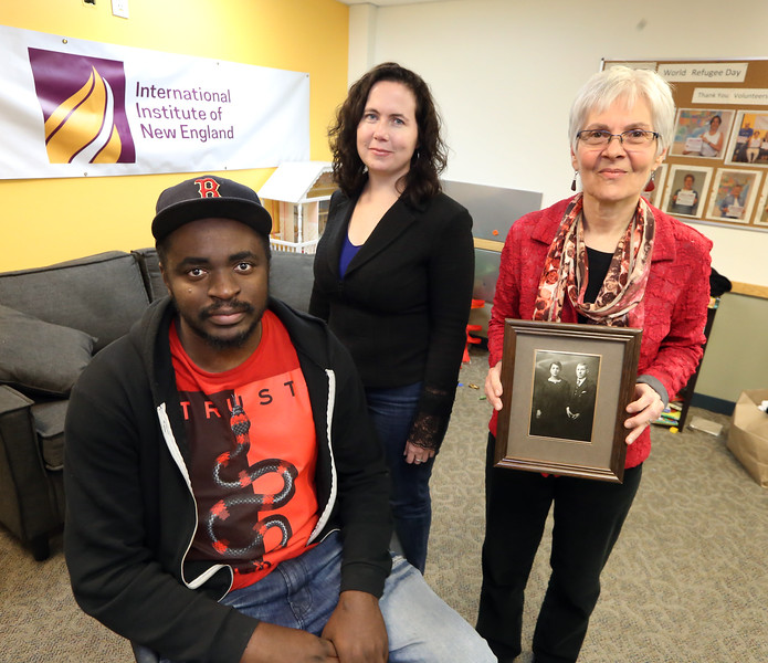 From left, Rodrigue Kalambayi of Lowell, who escaped from the Congo (DRC), Suitcase Stories director Cheryl Hamilton of Medford, and Szifra Birke of Lowell, holding a picture of her maternal grandparents, Szifra and Lazer Dymantsztajn, of Poland, who died in the Holocaust, at the International Institute of New England.  (SUN/Julia Malakie)