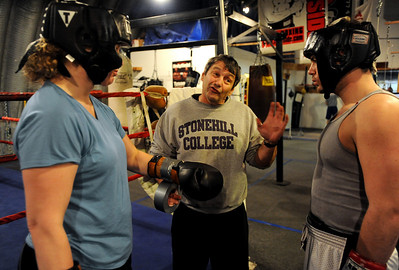 Trainer Dave Gaudette, center, has some advice for Chris Johnson, right, as Tawnia Wormell looks on at Front Range Boxing Academy. Cliff Grassmick / November 12, 2009