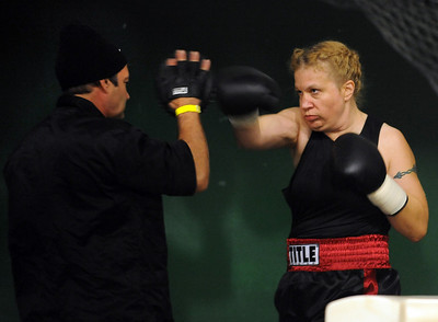 Trainer Dave Gaudette gets Tawnia Wormell warmed up before her first bout, a three round (one minute rounds) bout with Rachel Griego of Ft. Collins. Cliff Grassmick / November 12, 2009