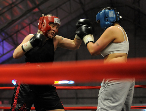 Tawnia Wormell, left, 42,  of Longmont,  throws a punch at Rachel Griego in her first professional fight.<br /> Cliff Grassmick / November 12, 2009