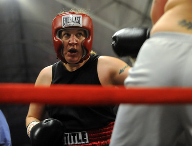Tawnia Wormell, 42, throws a punch at Rachel Griego in her first professional fight. Cliff Grassmick / November 12, 2009