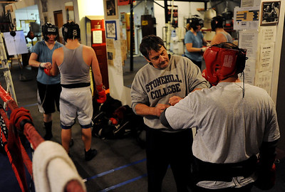 Tawnia Wormell, far left, prepsChris Johnson before a workout at Front Range Boxing Academy. Trainer  Dave Gaudette works with Oscar Martinez on the right. Cliff Grassmick / November 12, 2009