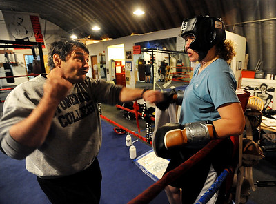 Trainer Dave Gaudette tells Tawnia Wormell where her hands should be during instruction at the Front Range Boxing Academy. Cliff Grassmick / November 12, 2009