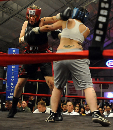 Tawnia Wormell, left,  of Longmont,  throws a punch at Rachel Griego in her first professional fight.<br /> Cliff Grassmick / November 12, 2009