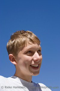 teenage boy having fun - portrait against a blue sky - adobe RGB