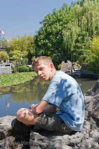 Teenage Boy resting in a Chinese Garden - Dr. Sun Yat-Sen Classical Chinese Garden, Vancouver, British Columbia, Canada