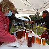 Second last Tuesday Tewksbury Community Market, at the field across from the Tewksbury Public Library. The last market will be Tuesday, Sept. 22, 4-7pm. Terry and husband Joe Pino, filling in for their friends Julie and Mike Kelley who own Tewksbury Honey, wrap a jar of honey for customer Paula Lunn of Tewksbury. (SUN/Julia Malakie)