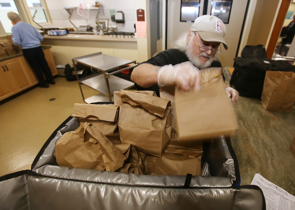 . Tewksbury Meals on Wheels volunteers prepare lunches for delivery, at the Tewksbury Senior Center. Gator Gosselin of Tewksbury fills a cooler with bags that contain milk, bread and dessert. (SUN/Julia Malakie)