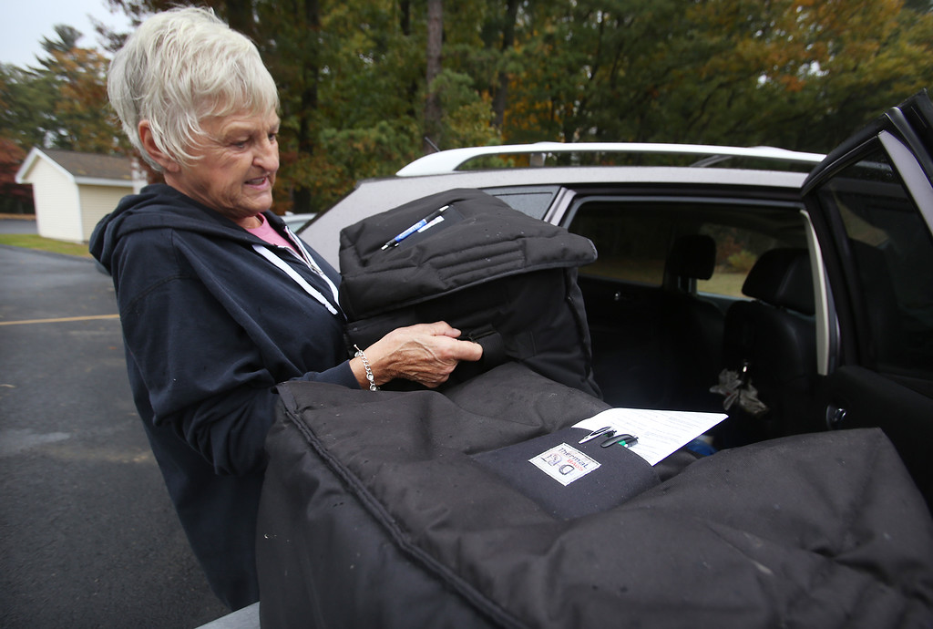 . Tewksbury Meals on Wheels volunteers prepare lunches for delivery, at the Tewksbury Senior Center. Volunteer driver Linda Murray of Tewksbury loads her car. (SUN/Julia Malakie)