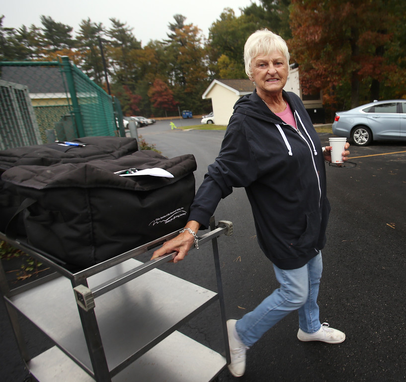 . Tewksbury Meals on Wheels volunteers prepare lunches for delivery, at the Tewksbury Senior Center. Volunteer driver Linda Murray of Tewksbury heads to her car. (SUN/Julia Malakie)