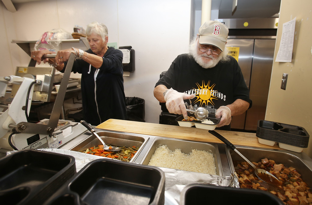 . Tewksbury Meals on Wheels volunteers prepare lunches for delivery, at the Tewksbury Senior Center. Volunteer Linda Murray, left, seals trays as Gator Gosselin fills them. Both are from Tewksbury.(SUN/Julia Malakie)