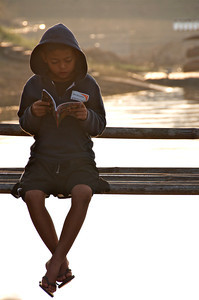 Reading by the reservoir at sunrise. Sangklaburi, Thailand