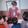Me (Sara) showing my Basic Reading class a gecko we found on the wall ( the gecko is on my thumb) 2000
