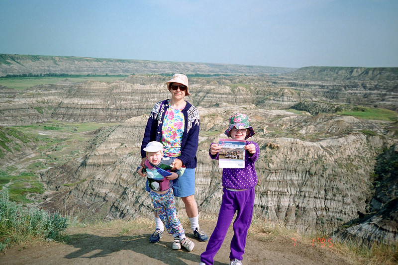 "Jacob, Ruth, and Helen on the edge of the Drumheller Valley in southern Alberta.  In the summer of 1995, we drove across Canada to attend a kids paleontology camp that dug for fossils in the famous Drumheller dinosaur beds.  Helen and Jacob both enjoyed pawing through bentonite clays looking for fossilized bone and tooth fragments. On this same trip, we visited the acclaimed Tyrrell Museum of Palaeontology which at the time was the finest museum of its type that I had ever seen.  I'd say the ""reconstructed"" Dinosaur National Monument Museum in Utah is now in the same class. After visiting Drumheller and Calgary we drove south into Montana just in time to witness the death of my maternal grandfather Gert. He died unexpectedly during our visit turning our cross-country trip into a funeral trip. I have enjoyed or endured, many road trips but this one stands out."