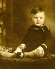 My recently deceased father as a pudgy toddler. It's important to remember people at many times during their lives. Dad died at 87 but he wasn't always an old man. I remember him as a young man and portraits like this take us back into his childhood.