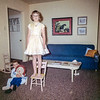 My sister Aileen standing on one of her toy chairs and my brother Steve hugging his Raggedy Ann Doll in our Redwash house living room. This snapshot is from my Grandmother Helen's collection but I suspect she didn't click the shutter. Helen had rigorous composition notions.  You had to pose just right and what's going on here is so wrong: that's why I love it.<br /> <br /> P.S. my dad still has the tacky panther print on the wall. Don't worry, it's safely hidden from human sight. My mother, like her mother before her, had the hoarding gene.