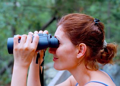 Mali looking through binoculars near the Wisconsin and Minnesota border.