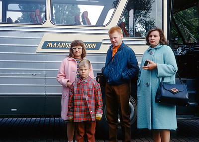 """Aileen, Steve, myself and our mother Evelyn beside a European tour bus in early 1968. My dad got lucky with this shot. Every person in this snapshot has a """"get this over with"""" look on their face. My brother and mother are particularly expressive.  He's grimacing and she's giving my dad the stink eye."""