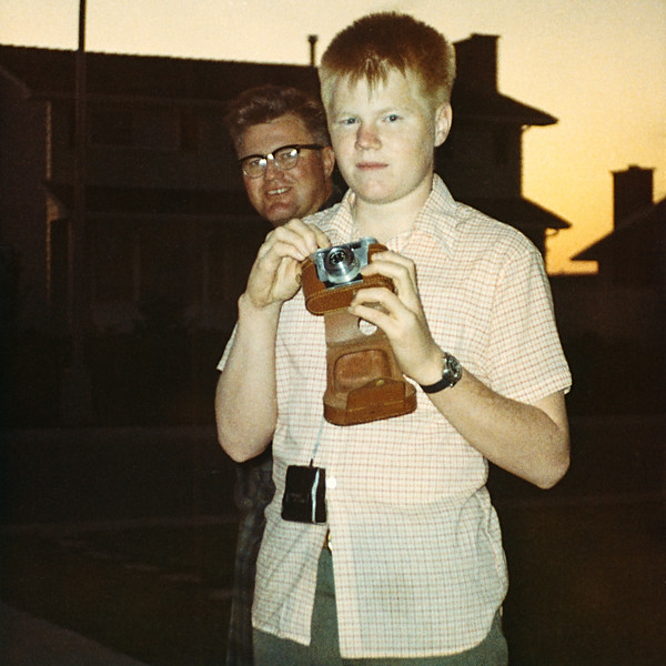 """I had to resist the urge to remove my dad's face from this old snapshot of me holding a 35mm Signet rangefinder camera in Edmonton in 1970. Photobombing was a thing long before the word """"photobombing"""" was a word. I got started with 35mm photography with that old rangefinder. It was old in 1970 having first belonged to one of my dad's uncles, then my dad, and then me. I used it until 2003 when the shutter finally froze. I wish I had held onto it. Old cameras make great decorations."""