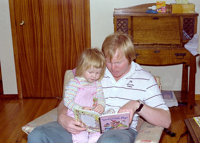 """Reading to Helen in our Glenburnie Ontario house around 1989.  Note that I am reading the Three Little Pigs a classic """"othering"""" tale about pinky white pigs enduring home invasions by a big bad black wolf.  Of course, only the industrious, (not on welfare or looking for handouts), pig foils the rapacious wolf.  And, you thought it was a harmless little children's story; woke up people!"""