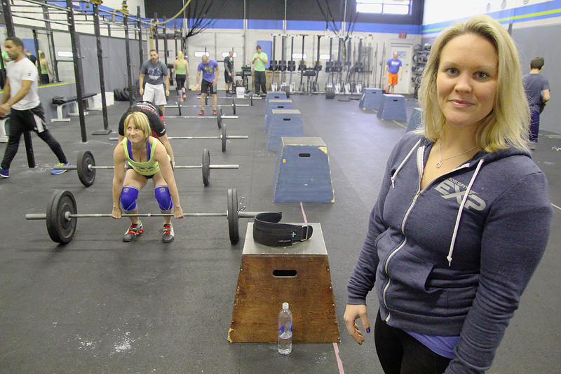 Tiffany Normandin, of Leominster, coaches at the CrossFit studio on Crawford Street in Leominster. She did the Whole 30 and as a result has changed her entire life around and has cut out sugar and carbs. She instructs a class on Wednesday afternoon at the studio and you can see them working out in the background. SENTINEL & ENTERPRISE/JOHN LOVE