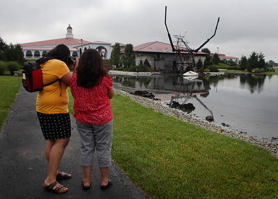 "Anjali Patel of Villa Park, Calif., left, photographs what is left of the ""King of King's"" statue of Jesus Christ outside the Solid Rock Church in Monroe, Ohio. The six-story-tall statue of Jesus with his arms raised along a highway was struck by lightning in a thunderstorm Monday night, June 14, 2010 around 11:15 p.m. and burned to the ground, police said. She said that she photographs the statue every year when she visits her aunt, Nayanay Patel, right, of Monroe. ""This is very sad. We had to get pictures,"" said Anjali Patel. (AP Photo/The Cincinnati Enquirer, Carrie Cochran) MANDATORY CREDIT"