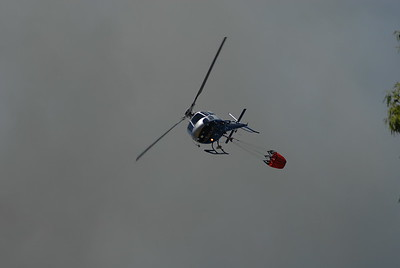 © Joseph Dougherty. All rights reserved.   The Regional Parks rescue helicopter banks sharply as it approaches its water drop target, with the heavy bag swinging like a pendulum below.