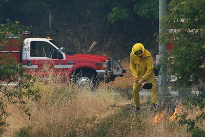 © Joseph Dougherty.  All rights reserved.   A fire fighter moves quickly to snuff out a spark that jumped across Tunnel Road from the main body of the fire.