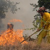 © Joseph Dougherty. All rights reserved.   A member of the fire fighting ground crew works to snuff out the leading edge of the fire as it licks through the dry grass of a steep hillside.