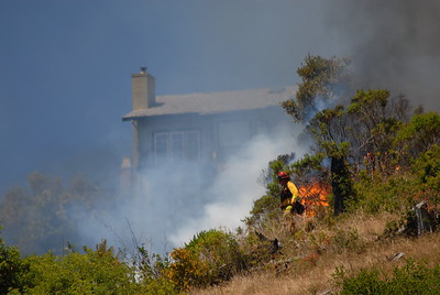 © Joseph Dougherty. All rights reserved.   Houses are seen in the background as a fire fighter walks beside the fire line.