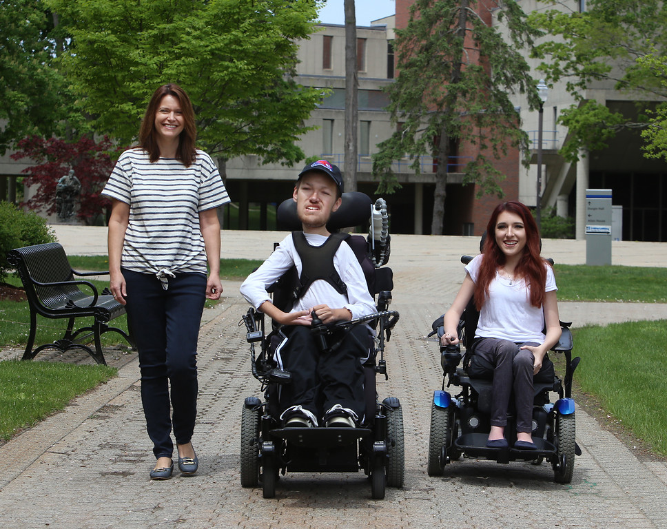 . UMass Lowell graduating senior and math major  Nicholas Raymond, 22, who has spinal muscular atrophy, his sister, rising junior and psychology major Elizabeth Raymond, 19, and their mother Kathy Raymond of Chelmsford, at UML South Campus. (SUN/Julia Malakie)