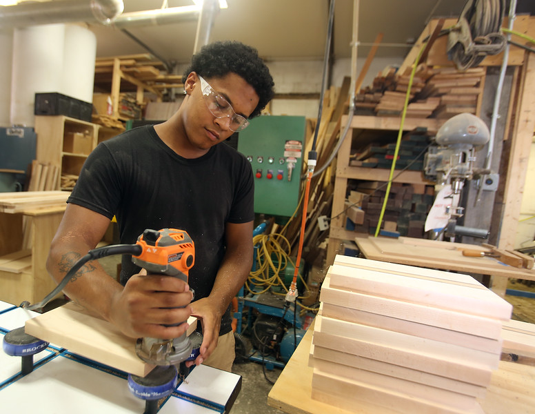 Culinary, woodworking and child care ares at UTEC, which is now in its 20th year. Marcos Estevez, 21, of Haverhill, smooths edges of cutting boards. (SUN/Julia Malakie)